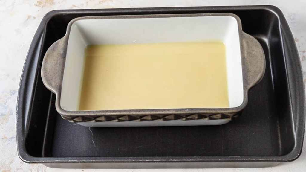 a pan with condensed milk inside of a larger roasting pan.