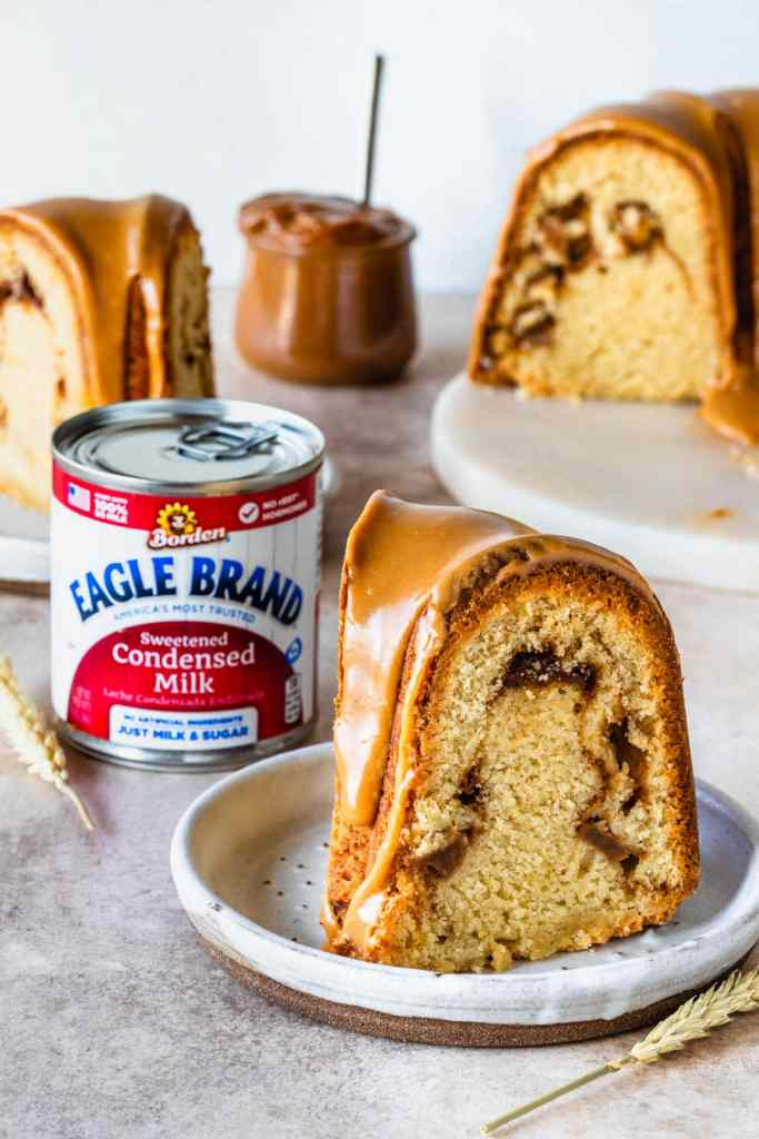 slice of apple cake with a caramel drizzle, and a can of condensed milk in the back.
