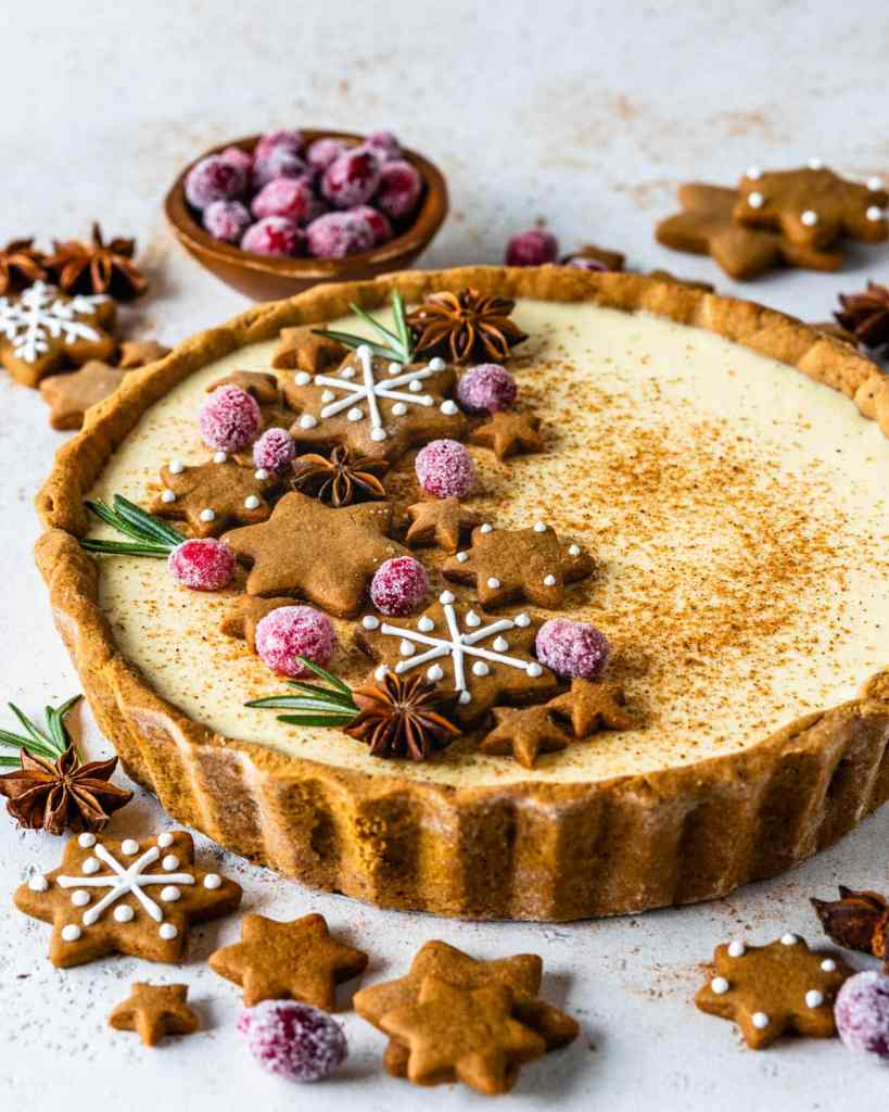 Eggnog Pie topped with gingerbread cookies, rosemary sprigs and sugared cranberries.
