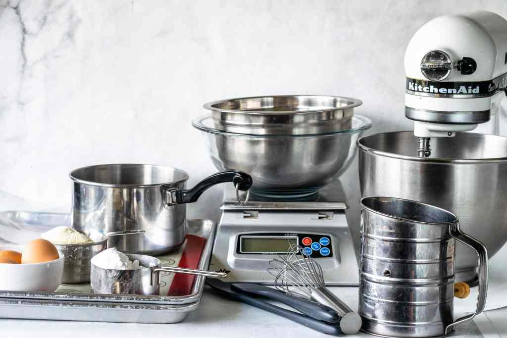 tools gathered for making macarons, mixer, small pan, eggs, scale, sifter.