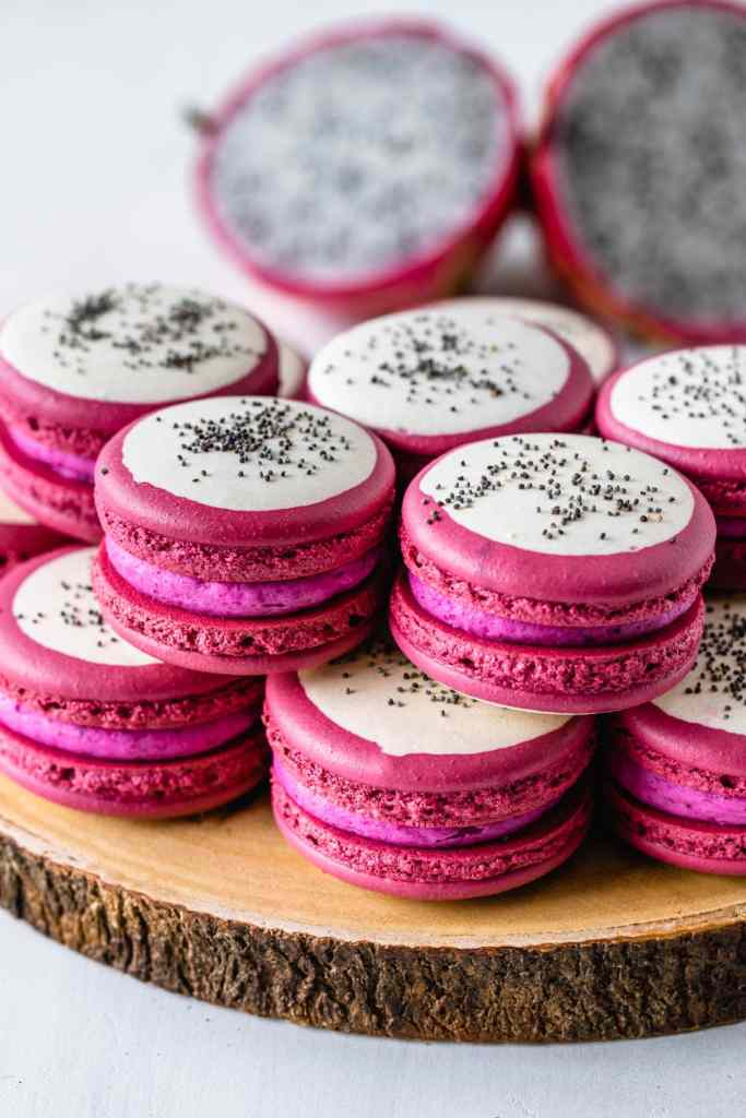 Dragon Fruit Macarons with a bicolor shell, pink and white, and with poppy seeds on top to resemble dragon fruit.