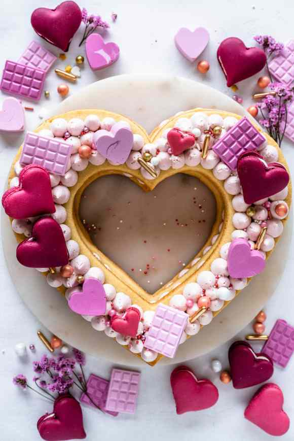 heart cookie cake topped with candy hearts, macarons, and sprinkles.