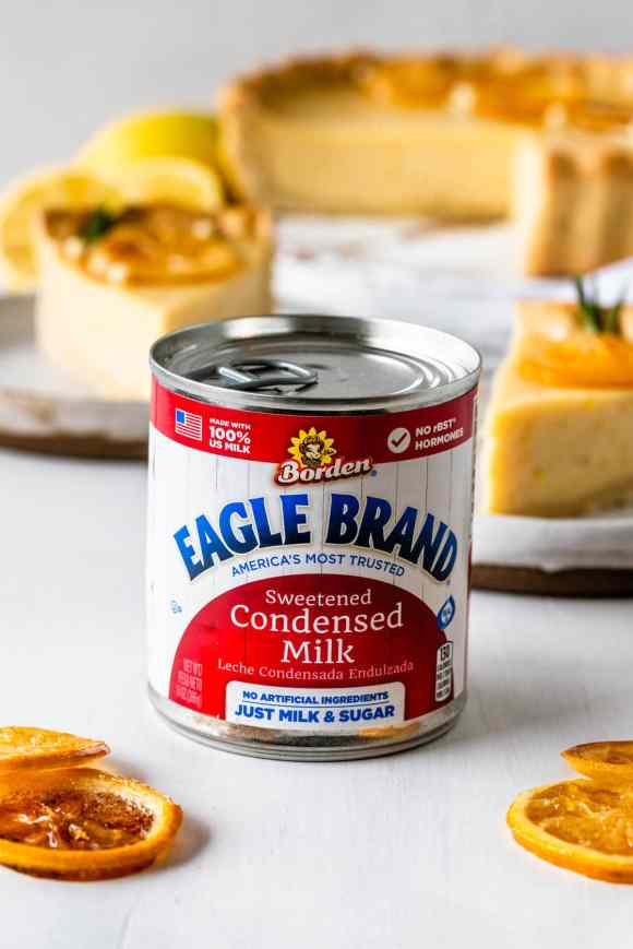 can of eagle brand® sweetened condensed milk with lemon slices on the side and a pie on the background.