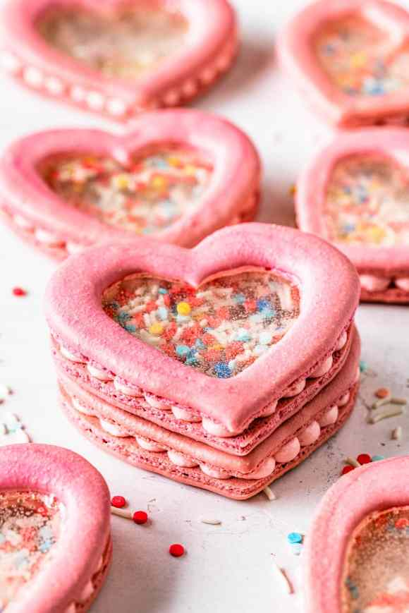stacked heart shaker macarons filled with sprinkles and they have a transparent middle.