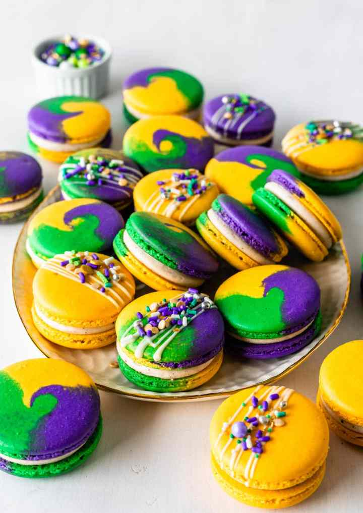 Mardi Gras Macarons  with purple, yellow, green shells, topped with sprinkles.