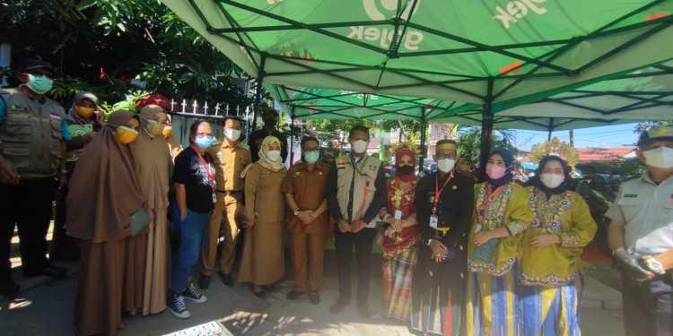Para panitia vaksin di Kelurahan Kampung Lette, Kecamatan Mariso, Makassar mengenakan pakaian adat Bugis Makassar menyambut peserta vaksin