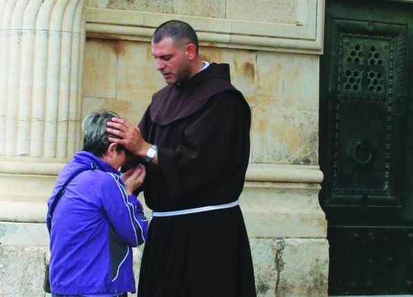 A pilgrim receives a blessing from a Franciscan friar in the Holy Land