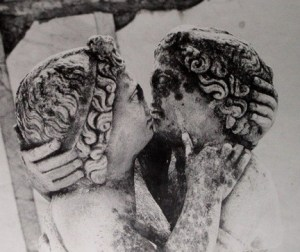 A kiss between ancient Romans. Statue of Cupid and Psyche