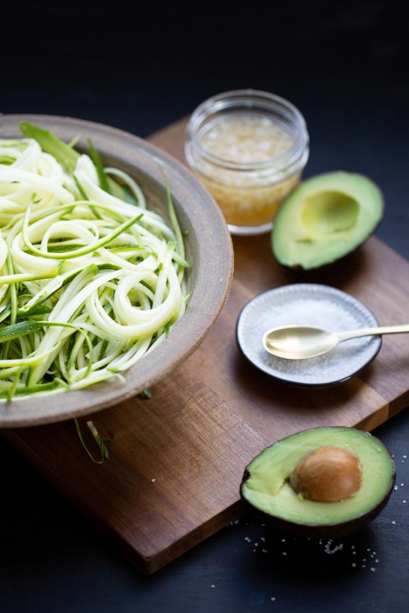 noodles de zucchini en tazón y un aguacate partido a la mitad
