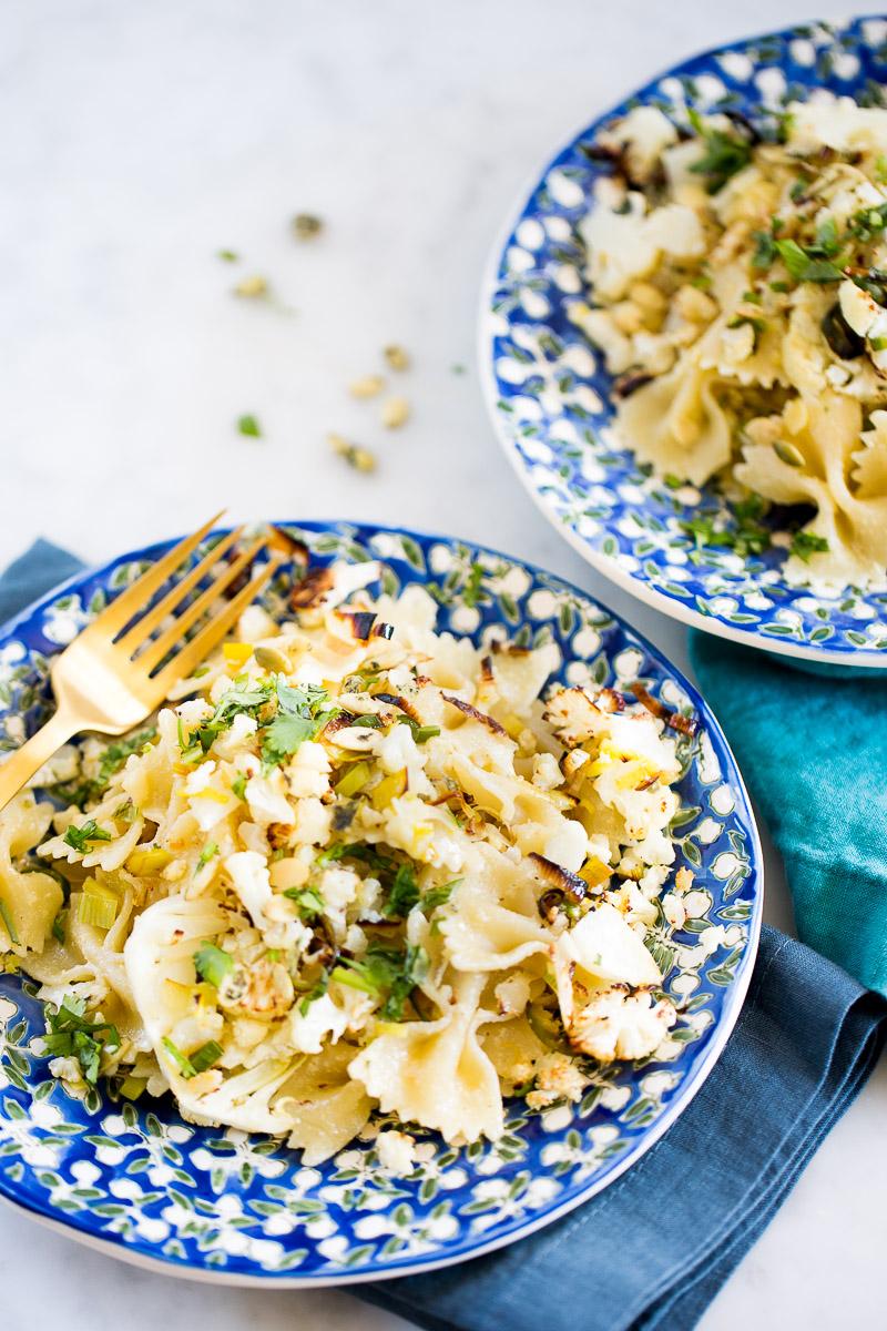 Pasta con coliflor y poro rostizada con aderezo de semillas de calabaza y limón. Receta vegana.