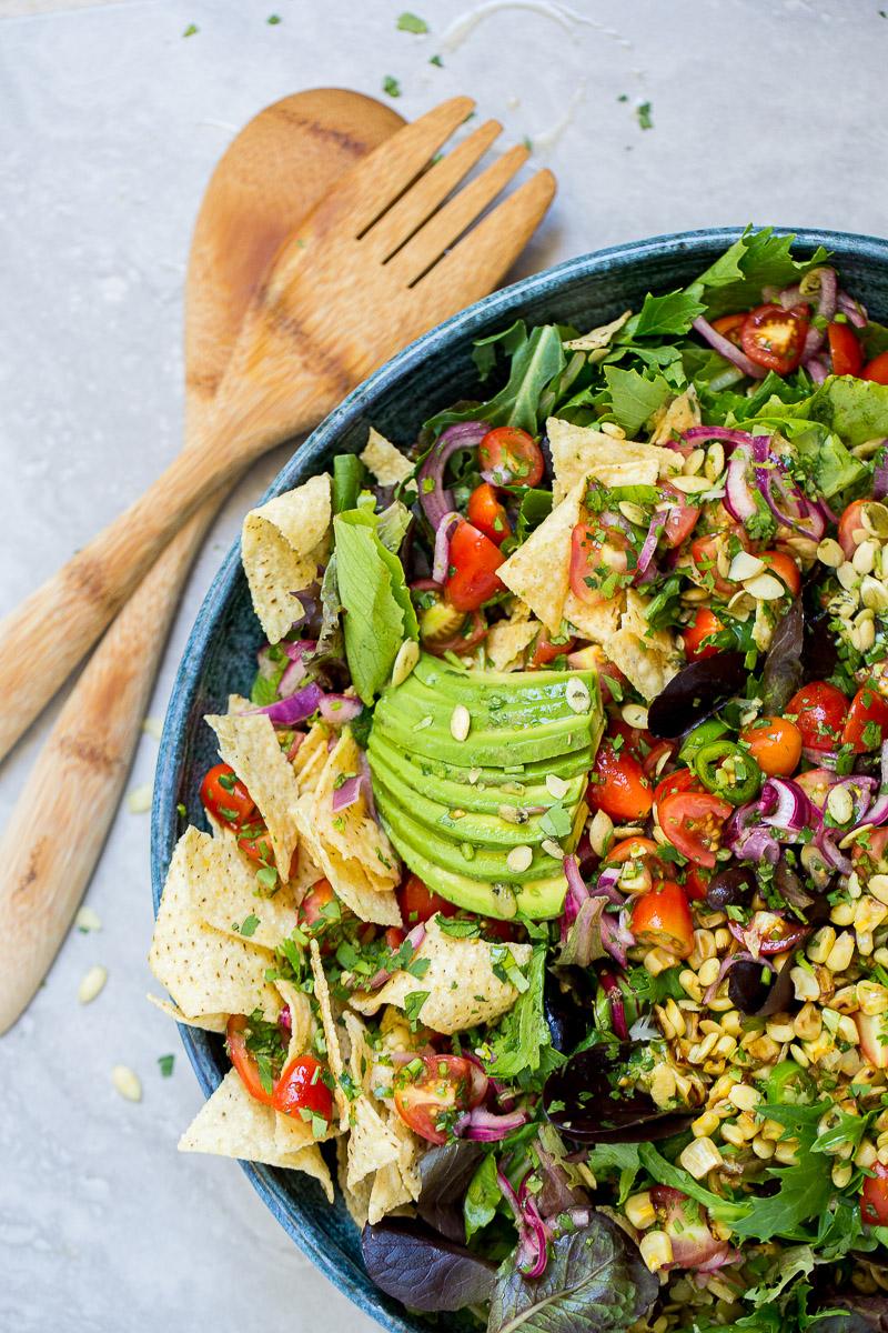 Taco salad en un platón con cucharas para servir a un lado