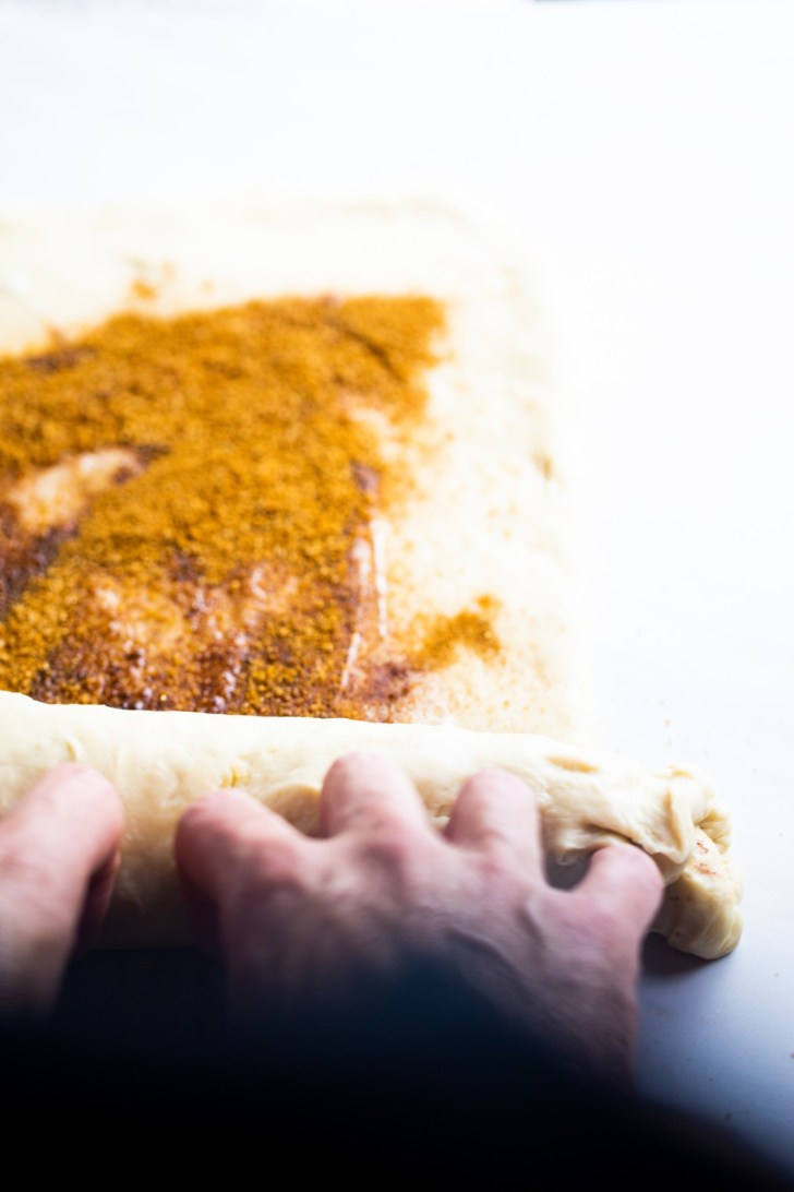 rolling a batch of dough for vegan cinnamon rolls