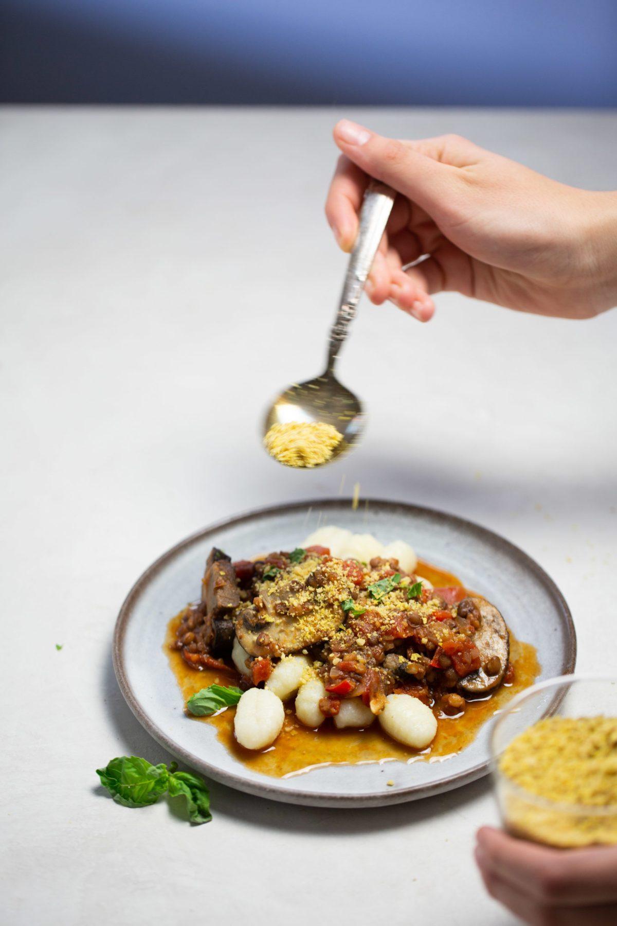 ragu vegano de lentejas y champiñón con queso parmesano vegano siendo espolvoreado encima