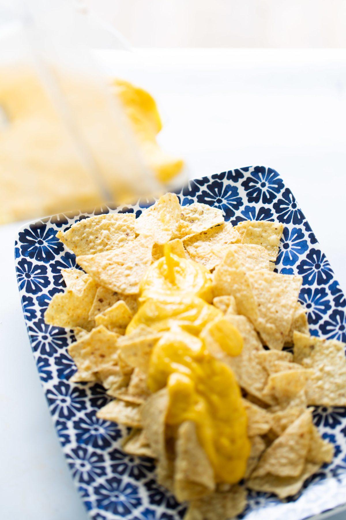 Pouring vegan queso ontop of nachos