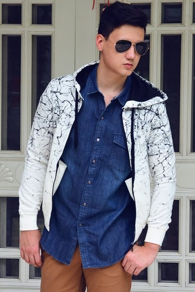 Update a rugged denim shirt and tan pants ensemble with a graphic black and white hoodie.