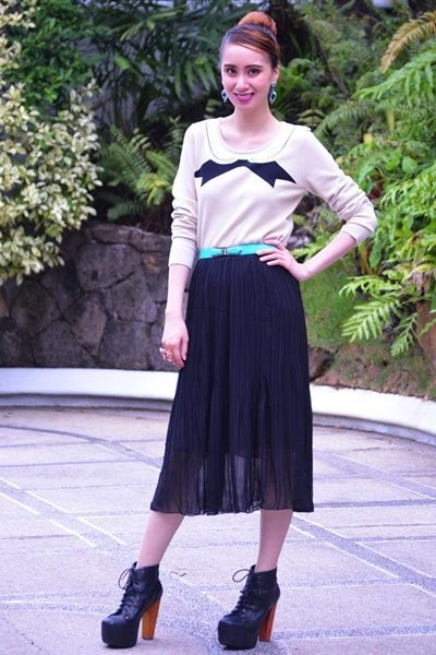 Embrace alterna-chic style by pairing Yishion's semi-sheer black pleated skirt with a bow-print lightweight top.