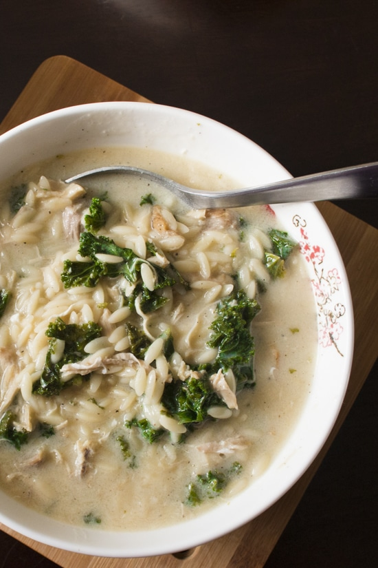 This hearty Greek lemon chicken soup is full of orzo, shredded chicken, and kale, and comes together in only 30 minutes. An easy avgolemono soup recipe! I can't believe how adding eggs to the broth makes it so creamy! Perfect for a quick and easy main course meal in the winter! | www.pinchmeimeating.com