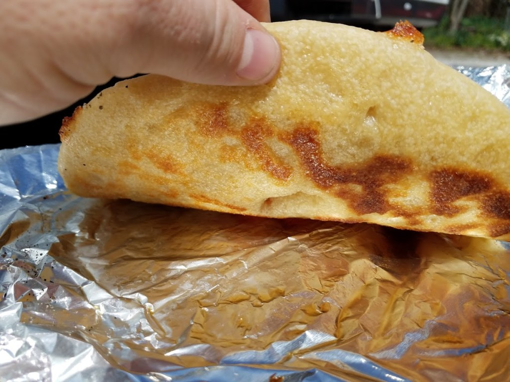 perfect crispy pizza crust lifted off a piece of foil to see a nice lightly browned crust