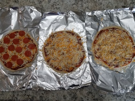 Three pizzas on foil and ready to be cooked. The left is a pepperoni and the other two are plain cheese.