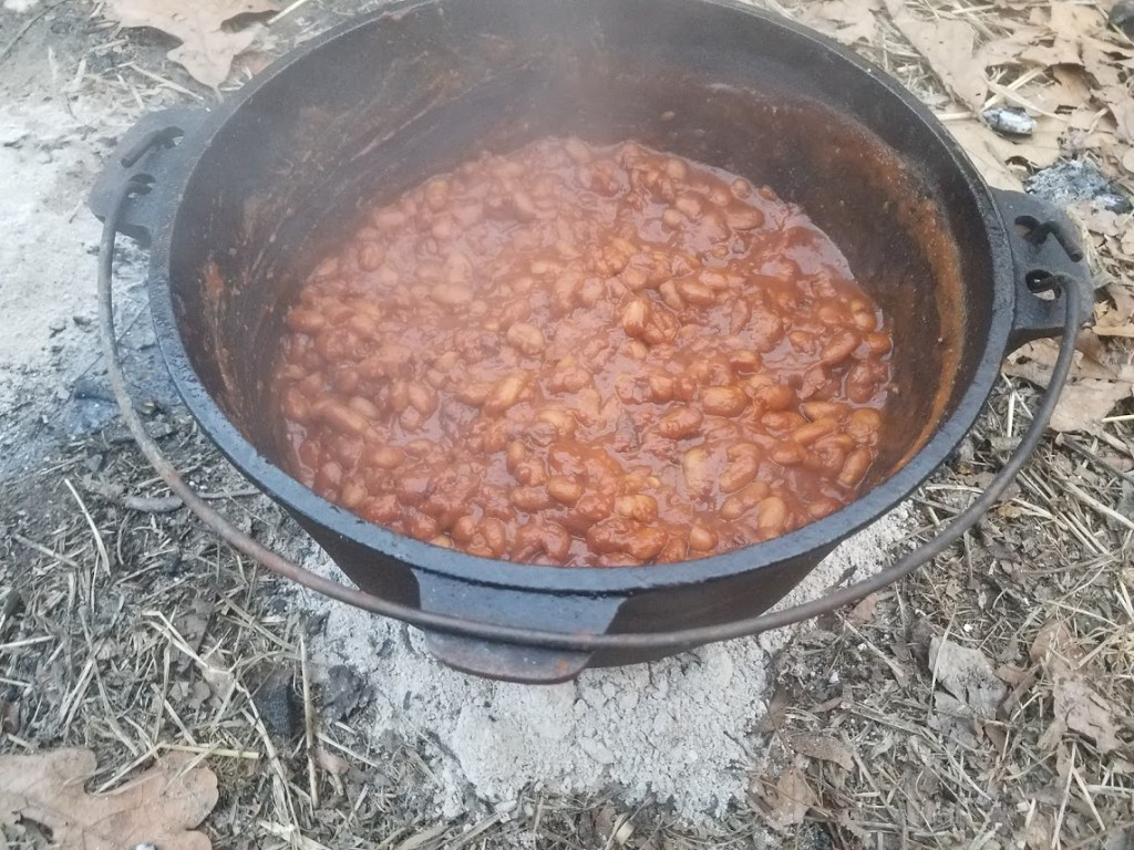 Baked beans in a dutch oven on the ground