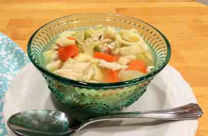 A bowl of Chicken Noodle Soup with spoon on a plate.