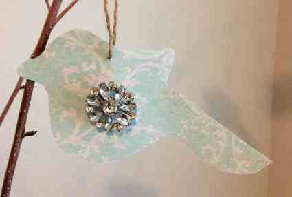 Paper bird with rhinestone decor hanging on a branch
