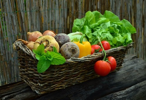 A basket filled with tomatoes, lettuce, peppers and other vegetables