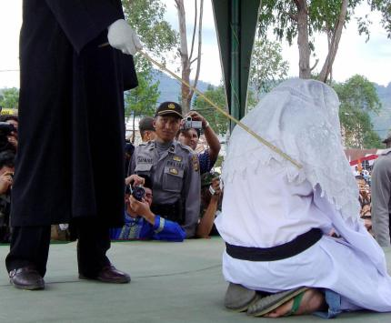 TAKENGON, INDONESIA: An Acehnese executor flogs a convicted woman in Takengon, in Indonesian central Aceh province, 19 August 2005 after an Islamic sharia court ordered four women to be flogged for petty gambling offences. The public lashing was the second since the Indonesian government allowed the western province to implement religious law as part of broader autonomy granted in 2001 to curb a separatist Islamist insurgency. AFP PHOTO (Photo credit should read STR/AFP/Getty Images)