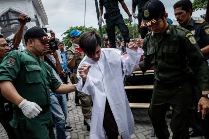 BANDA ACEH, INDONESIA - MAY 23: An indonesian man escorted by the sharia police after get caning in public from an executor known as 'algojo' for having gay sex, which is against Sharia law at Syuhada mosque on May 23, 2017 in Banda Aceh, Indonesia. The two young gay men, aged 20 and 23, were caned 85 times each in the Indonesian province of Aceh during a public ceremony after being caught having sex last week. It was the first time gay men have been caned under Sharia law as gay sex is not illegal in most of Indonesia except for Aceh, which is the only province which exercises Islamic law. The punishment came a day after the police arrested 141 men at a sauna in the capital Jakarta on Monday due to suspicion of having a gay sex party, the latest crackdown on homosexuality in the country. (Photo by Ulet Ifansasti/Getty Images)