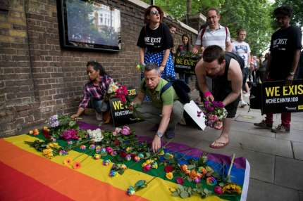 Demonstrators lay roses on a rainbow flag as they protest over an alleged crackdown on gay men in Chechnya