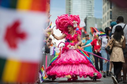 A drag queen high five's spectators during the Pride Parade in Toronto, Ontario, June 25, 2017. The event draws hundreds of thousands of spectators every year. / AFP PHOTO / GEOFF ROBINS (Photo credit should read GEOFF ROBINS/AFP/Getty Images)