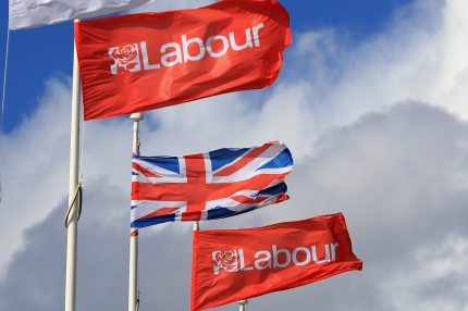 LIVERPOOL, ENGLAND - SEPTEMBER 25: The Union flag flies between Labour party flags during the Labour party conference at the ACC on September 25, 2016 in Liverpool, England. Party leader Jeremy Corbyn is rallying members hoping to re-unite the party after being re-elected leader yesterday. (Photo by Christopher Furlong/Getty Images)