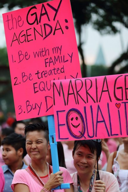 SINGAPORE - JUNE 30: Participants hold up placards during the 'Night Pink Dot' event arrange to increase awareness and understanding of the lesbian, gay, bisexual and transgender community in Singapore at Hong Lim Park on June 30, 2012 in Singapore. The event is the fourth annual gathering held in support of the freedom to love. (Photo by Suhaimi Abdullah/Getty Images)