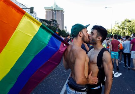 """A couple kiss as one of them holds a rainbow flag the WorldPride 2017 parade in Madrid on July 1, 2017. Revellers took to the rainbow streets of Madrid today in the world's biggest march for gay, lesbian, bisexual and transgender rights. Carried along by the slogan """"Viva la vida!"""" (Live life!), the parade of 52 floats started partying its way through the centre later afternoon in celebration of sexual diversity, under high security. / AFP PHOTO / OSCAR DEL POZO (OSCAR DEL POZO/AFP/Getty Images)"""