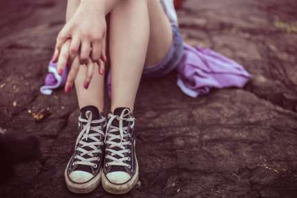Girl sitting holding her own hand, representing sadness for LGBT mental health