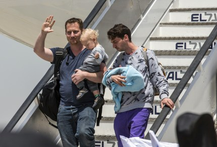 Israeli gay couple disembark plane after being repatriated from Nepal.