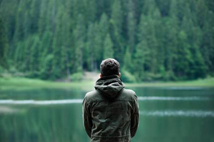 A man stares out at a lake