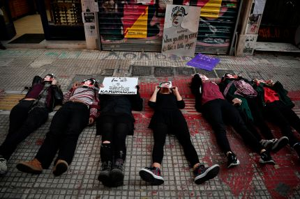 Activists lie down at the spot where gay activist Zak Kostopoulos was killed two month ago during a rally in Athens on November 24, 2018.