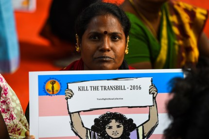 """A woman holding a placard reading """"kill the transbill"""""""