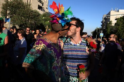 An Israeli couple kiss during the annual Jerusalem Pride Parade on July 21, 2016.