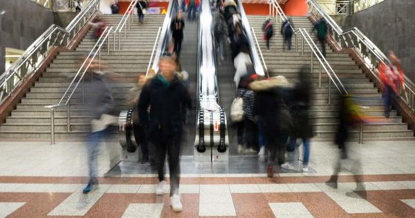 Transit riders are a blur in a subway station with stairs and an escalator.
