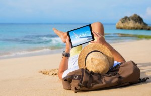 A man resting on a sandy beach while using his tablet device