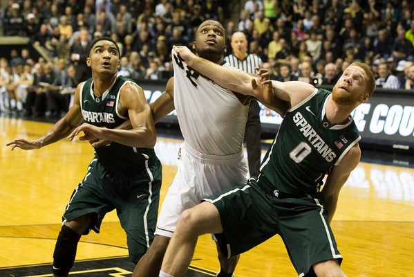 Michigan State's Gary Harris (14) and Russell Byrd (0) battle for a rebound with Purdue forward Errick Peck (32)