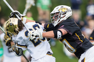 Mike Lowe checks Nick Ossello during the NCAA Lacrosse First Round game between the Notre Dame Fighting Irish and Towson Tigers at Arlotta Stadium on May 9, 2015