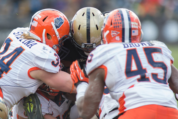 Brandon Cottom of Purdue tries to dive over the pile as Mike Svetina (34) and Jonathon Brown (45) defend