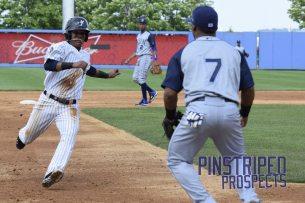 Thairo Estrada slides into third on a wild pitch in the first inning (Robert M. Pimpsner)