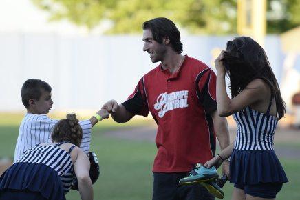 The Pinstripe Patrol congratulates an on-field game contestant (Robert M Pimpsner)
