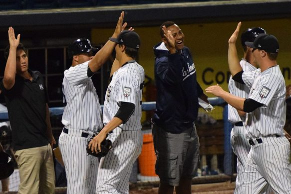 Domingo Acevedo and Luis Cedeno congratulates their teammates on their way back to the clubhouse (Robert M Pimpsner)