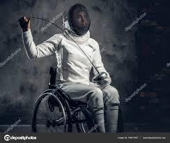 Na czarnym tle szermierz siedzący na wózku inwalidzkim, ubrany na biało w strój do walki trzyma w prawym ręku szpadę