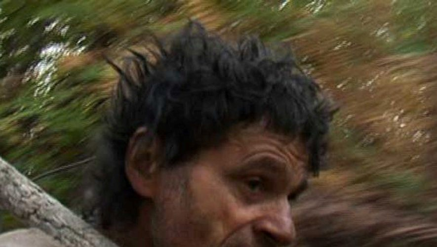 Głowa mężczyzny na tle liści drzew